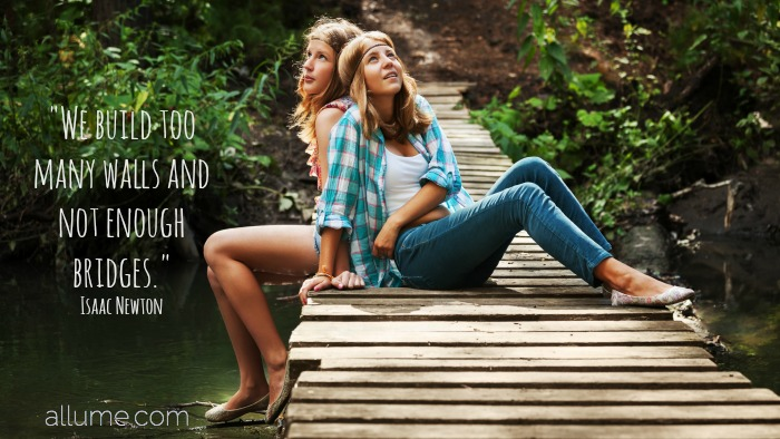Two young girls sitting on the wooden bridge